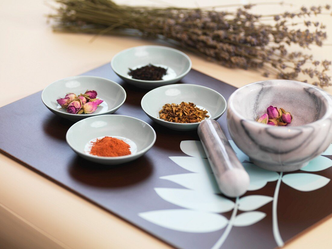 An arrangement featuring a mortar, a pestal, spices and dried herbs