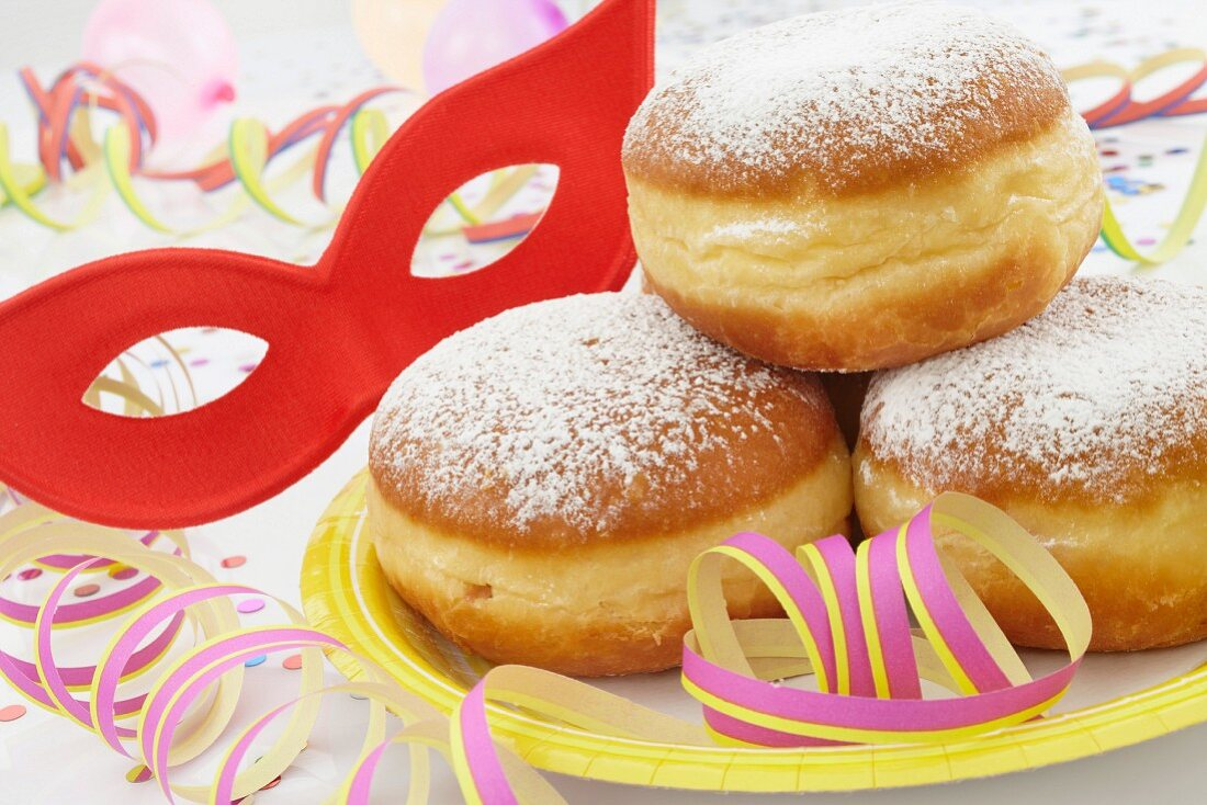 Doughnuts on a paper plate with streamers and a mask