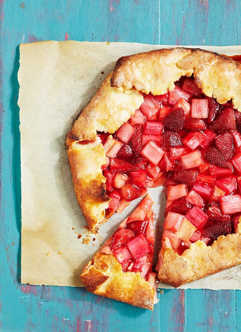 Sliced strawberry and rhubarb cake on a piece of baking paper