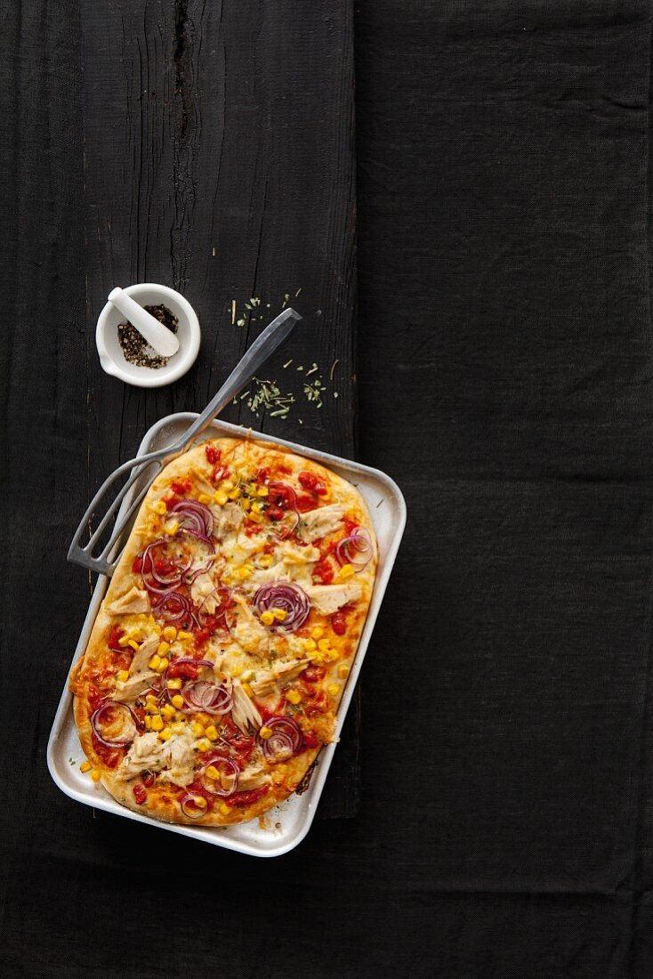 A spelt pizza with tomatoes, sweetcorn, tuna fish and red onions
