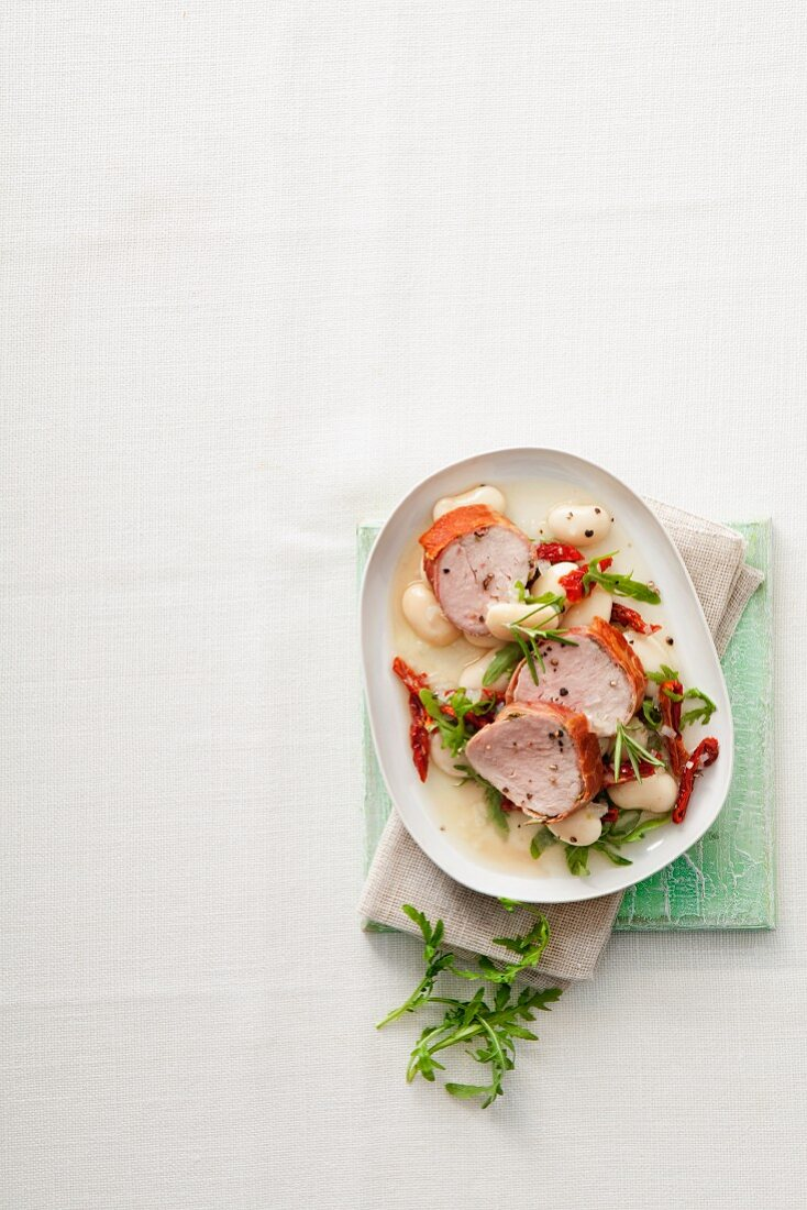 Pork fillets wrapped in Parma ham with white beans, rocket and dried tomatoes