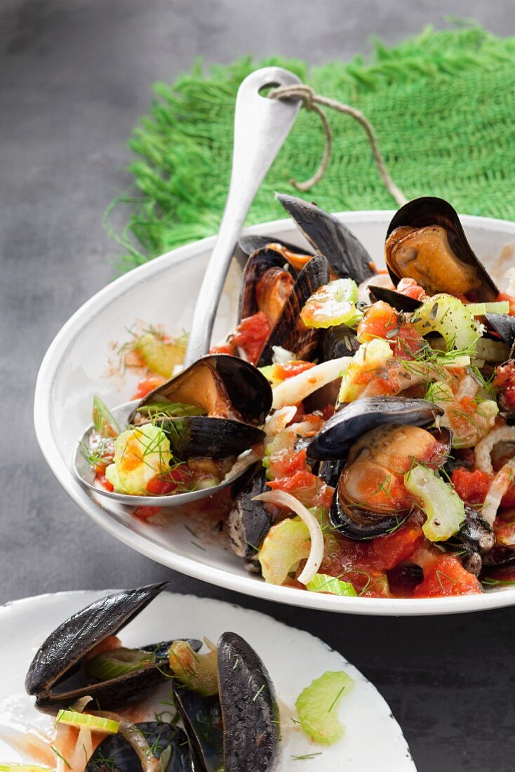 Mussels in a white wine broth with celery and tomatoes