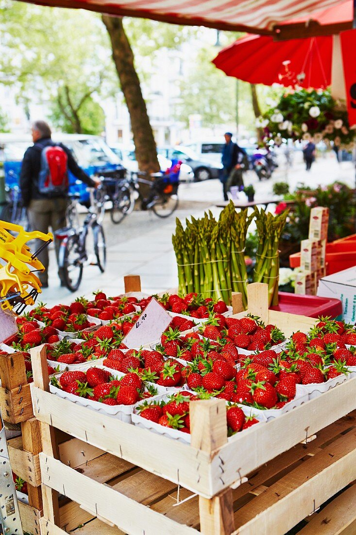 Strawberries and asparagus at a market stall
