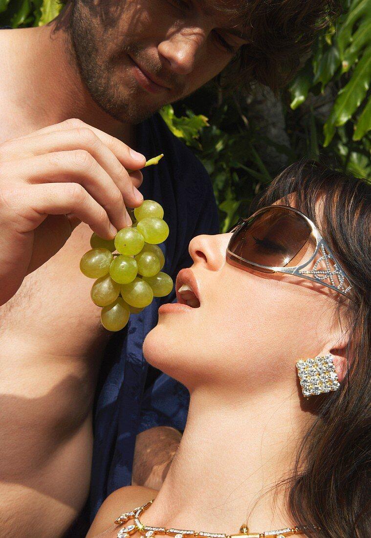 A man feeding a woman grapes