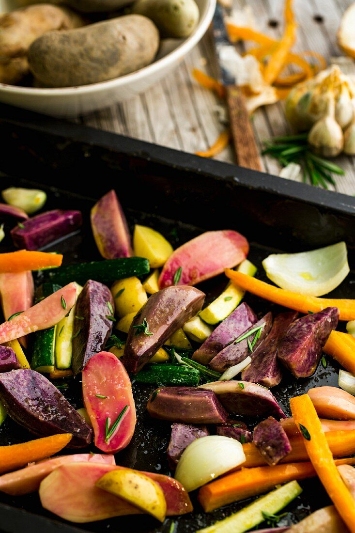 Vegetables with olive oil, rosemary, savory and fleur de sel on a baking tray