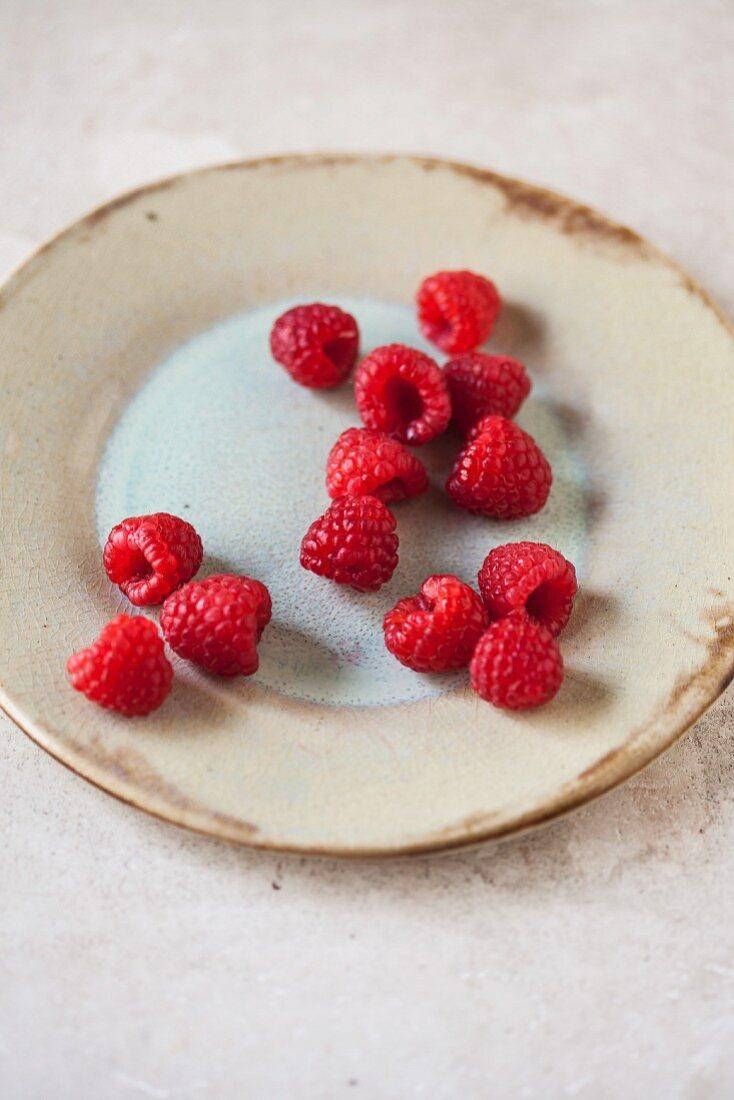 Fresh raspberries on a ceramic plate