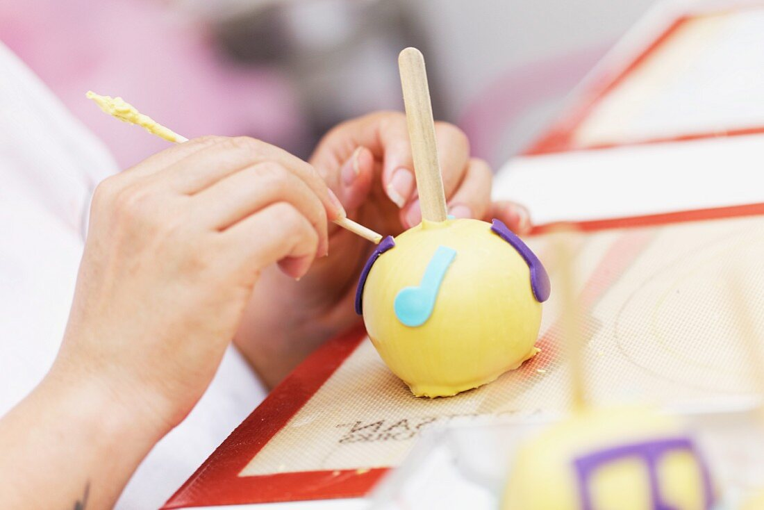 A giant cake pop being decorated with music notes