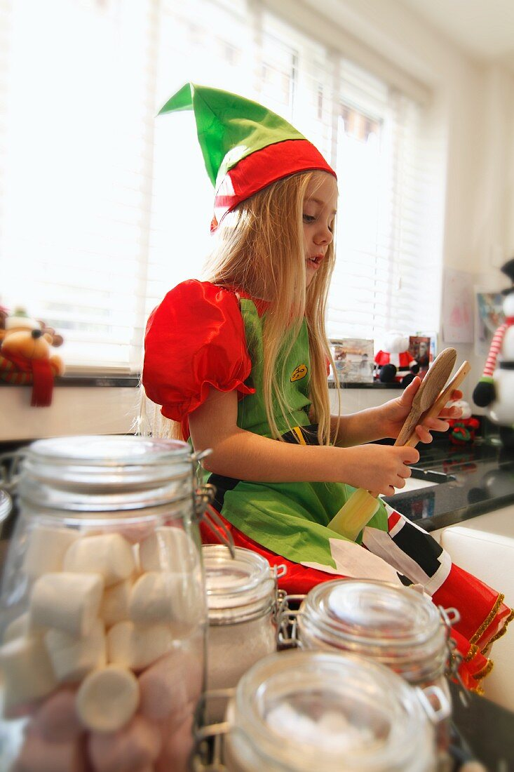 A girl dressed as a Christmas elf in a kitchen with baking utensils