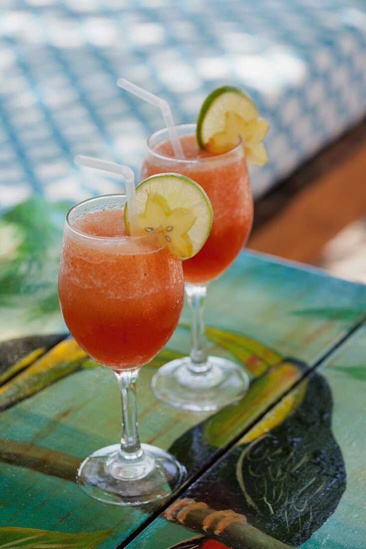 Two exotic drinks garnished with limes and star fruit
