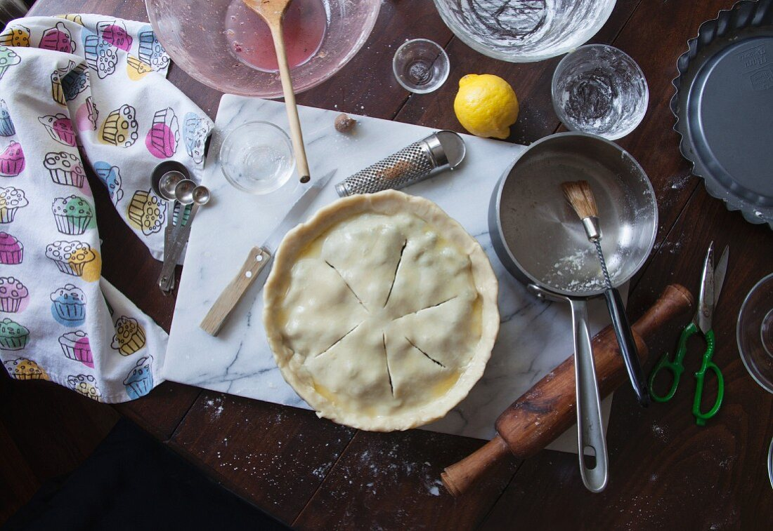 An unbaked blueberry pie, ingredients and baking utensils