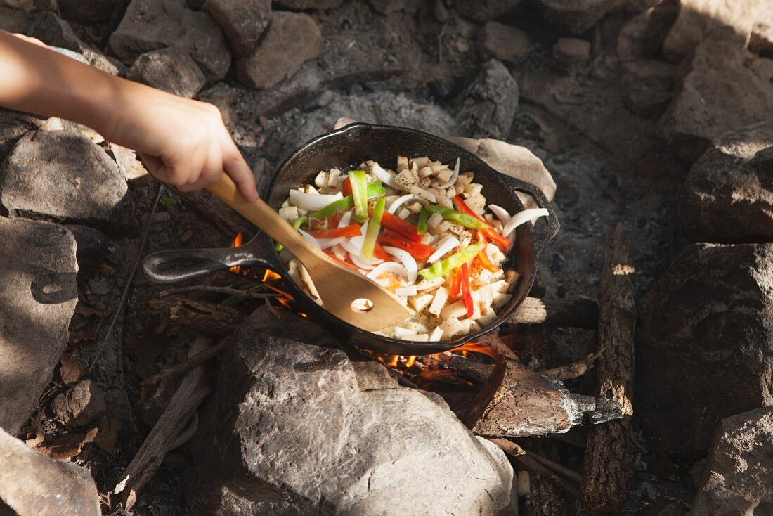 Young people cooking in a pan over a camp fire