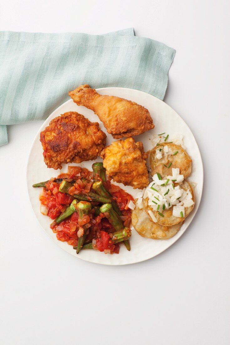 Fried chicken and roasted green tomatoes served with okra pods in tomato sauce