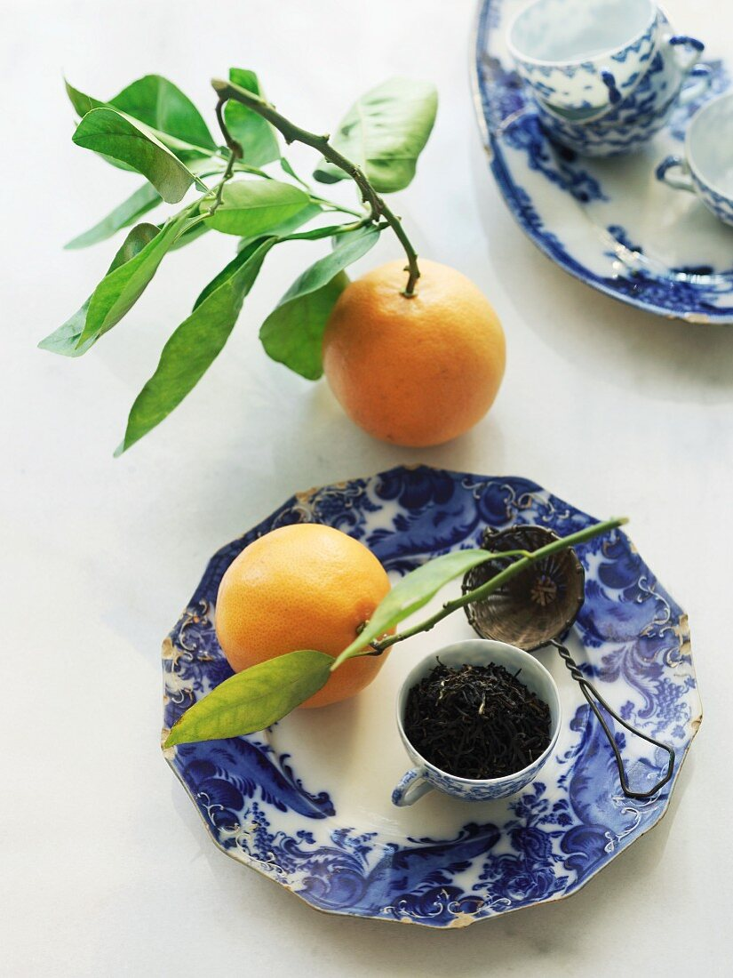 Orange pekoe black tea in a cup with a tea strainer and oranges