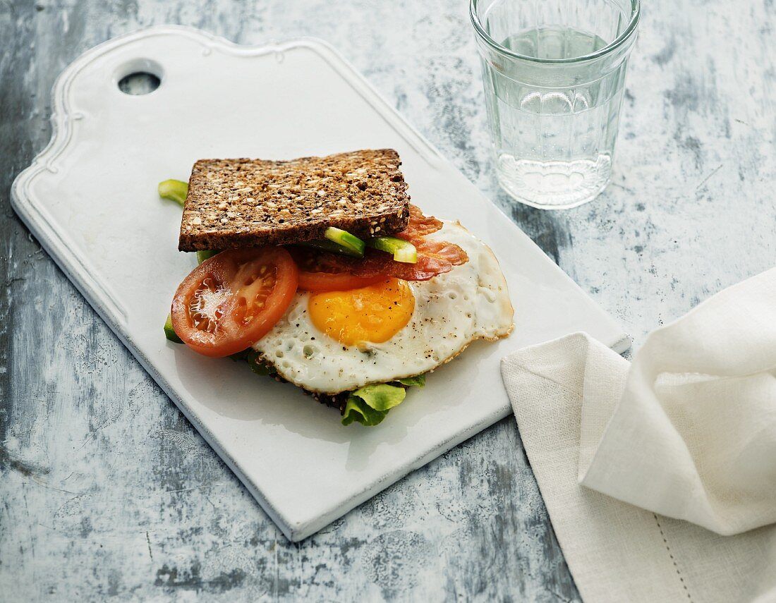 A wholemeal sandwich with fried egg and tomatoes
