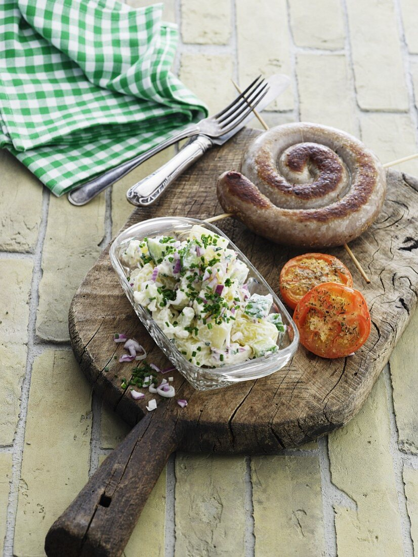 A spiral sausage with braised tomatoes and potato salad