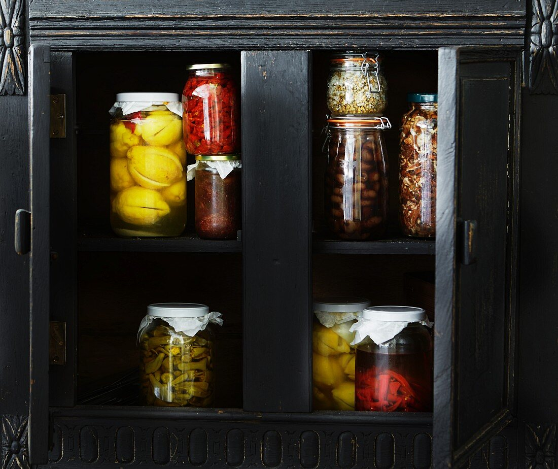 Various jars of preserves in a wooden cupboard