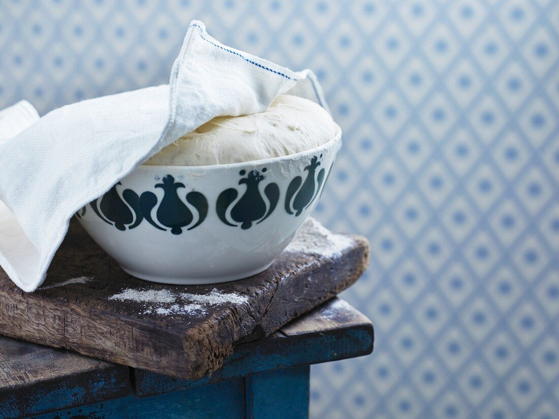 Yeast bread dough in a bowl under a teatowel