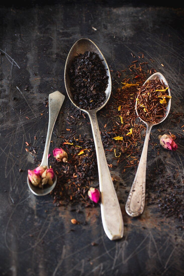 Dried black tea and rooibos with rose buds in vintage spoons on a black metal surface