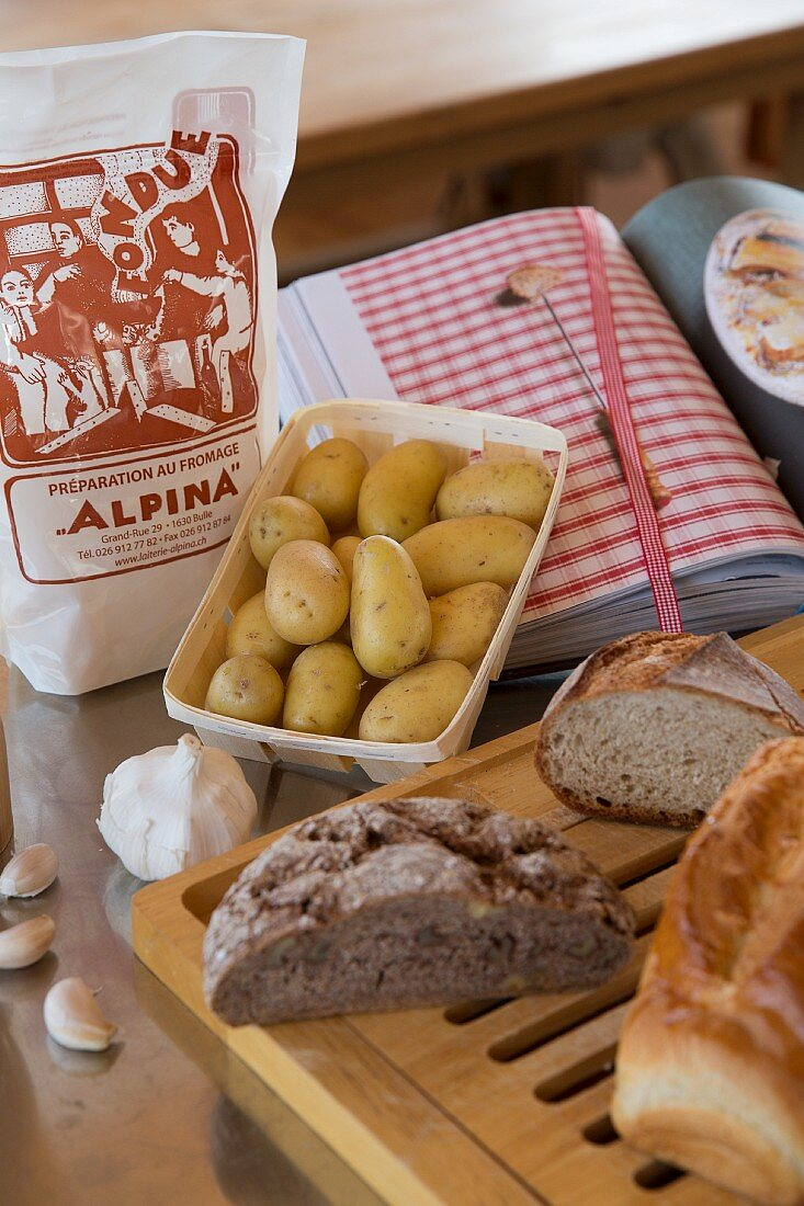 Bread on breadboard and dish of potatoes next to cookery book