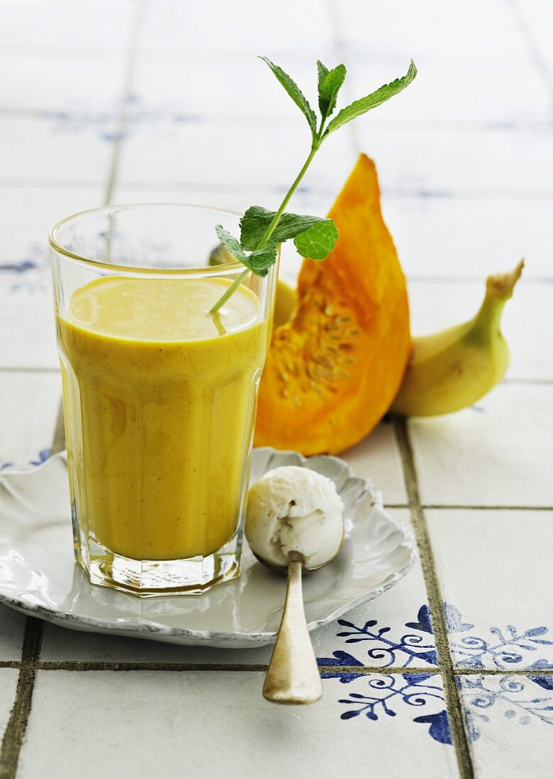 A pumpkin and banana smoothie with a scoop of ice cream on a spoon
