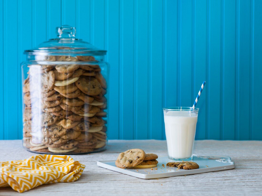 A giant cookie jar filled with chocolate chip cookies with a plate of cookies and milk in the foreground