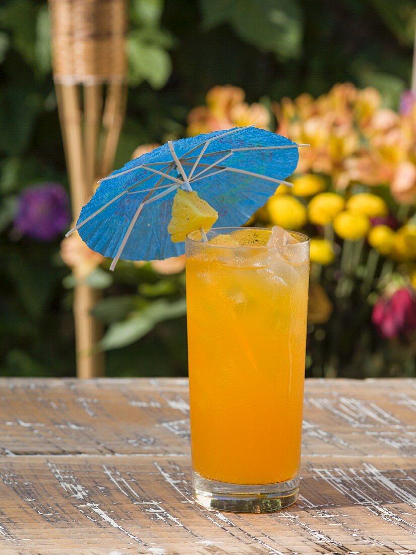 Erfrischender Fruchtcocktail mit Ananas und Cocktailschirmchen