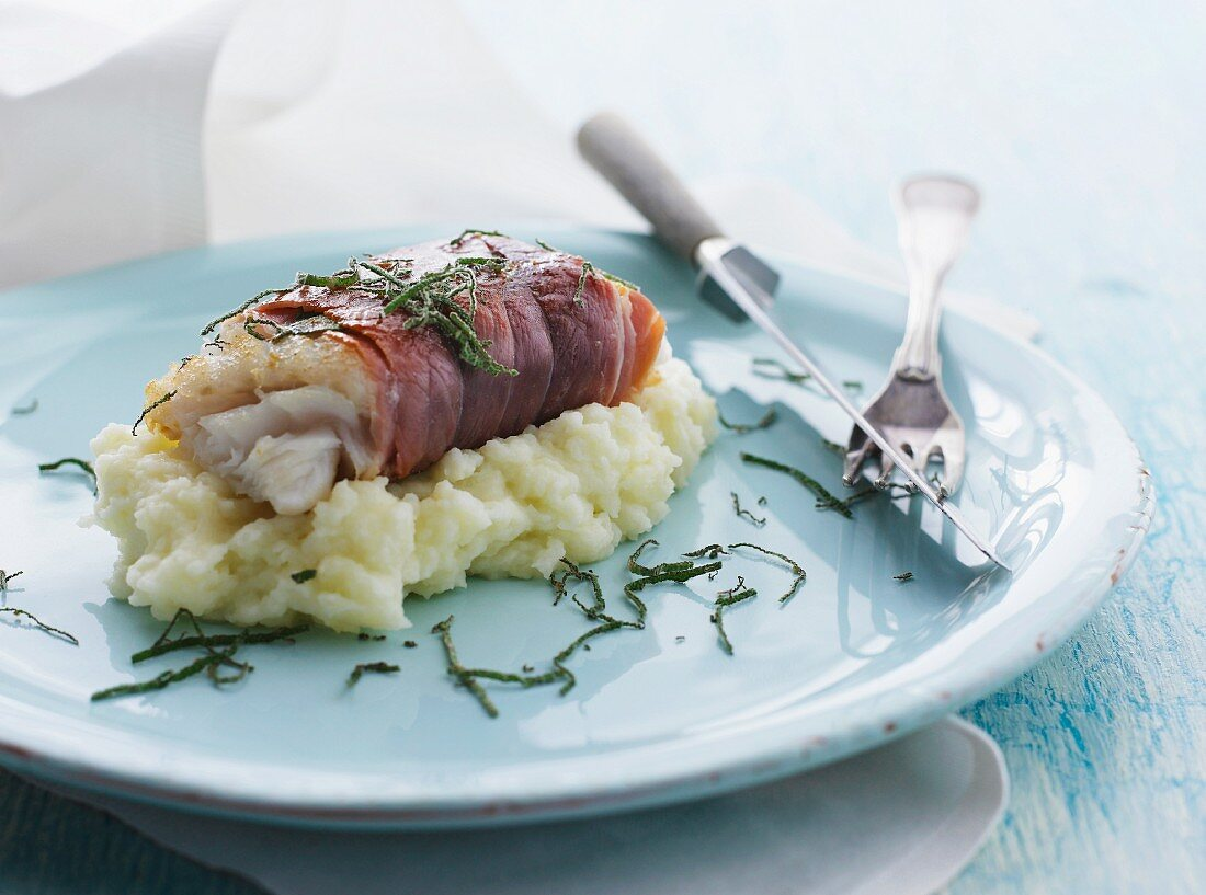 Cod fillet wrapped in smoked ham with sage on cauliflower purée