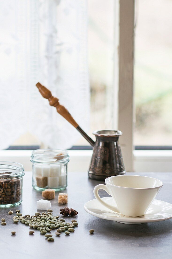 A coffee cup, sugar cubes and unroasted coffee beans on a kitchen table