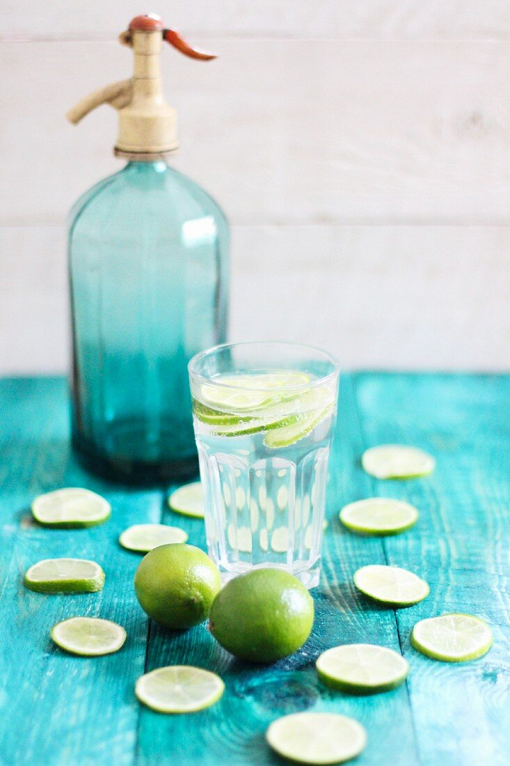 A glass of water with lime slices with a blue siphon bottle in the background