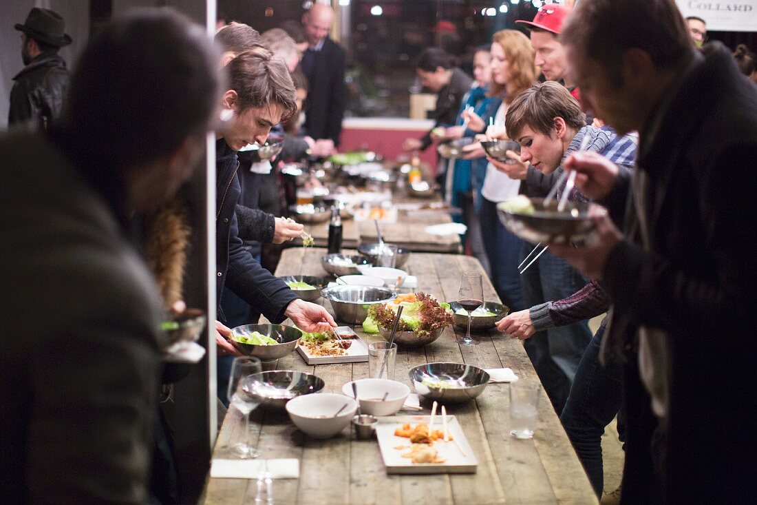 Guests at a Schlachtfest (country feast to eat up meat from freshly slaughtered pigs) in a market hall (Berlin)