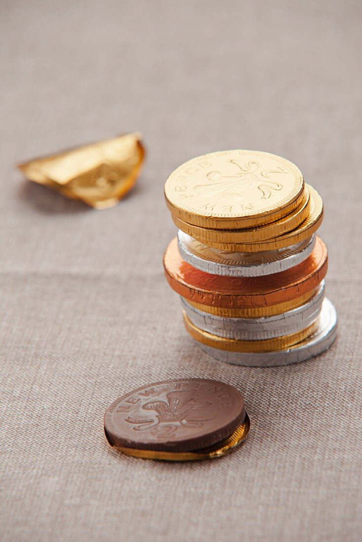 A stack of chocolate coins in foil on a tablecloth