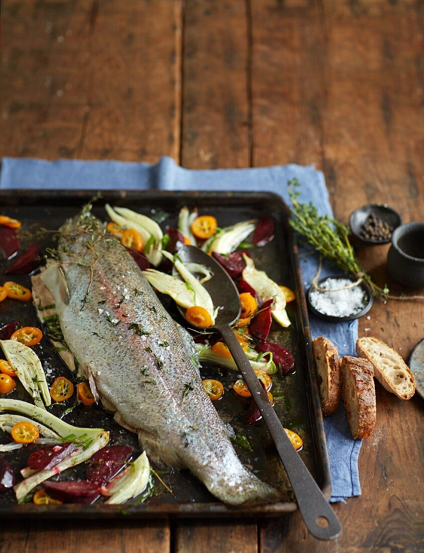 Marinated salmon trout with vegetables on a baking tray