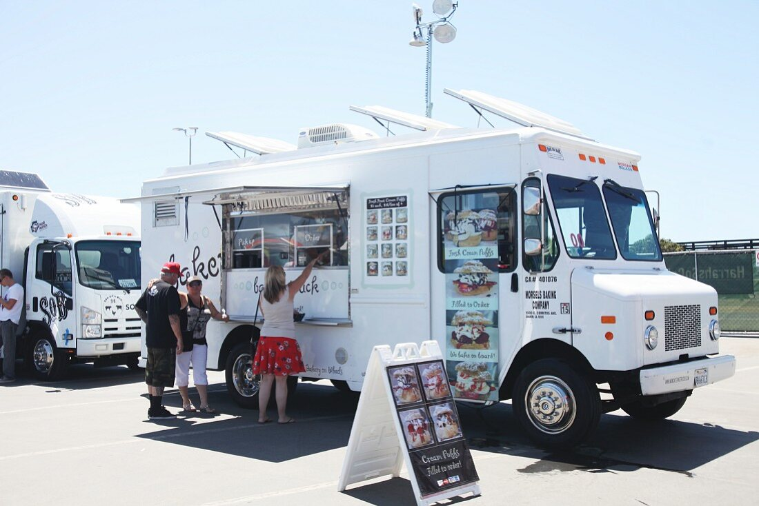 Customers buying sweets at a food truck festival in California, USA