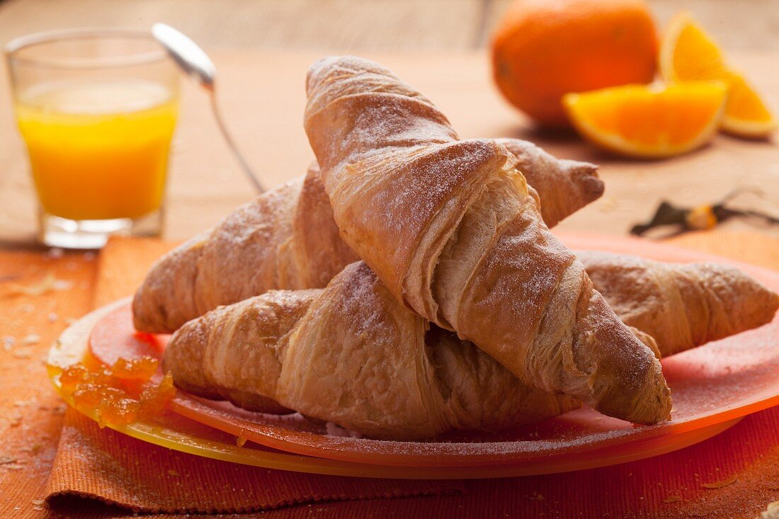 Fresh croissant with jam served with freshly squeezed orange juice
