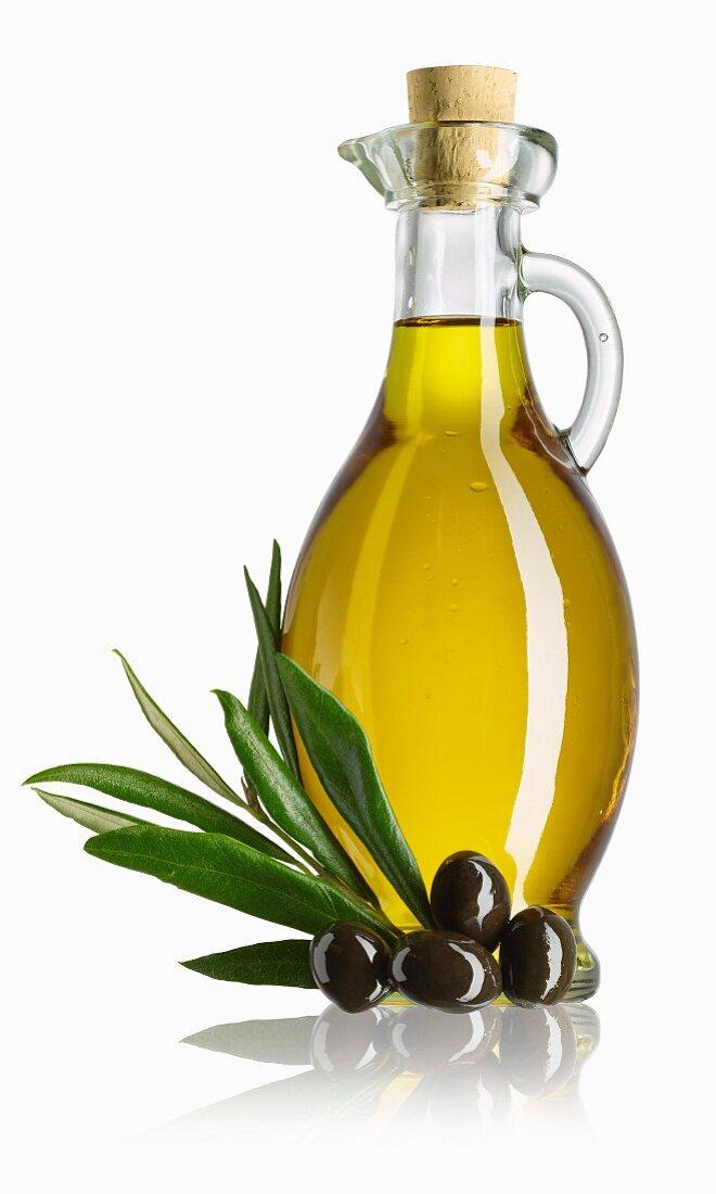 A carafe of olive oil, a sprig of olive leaves and black olives