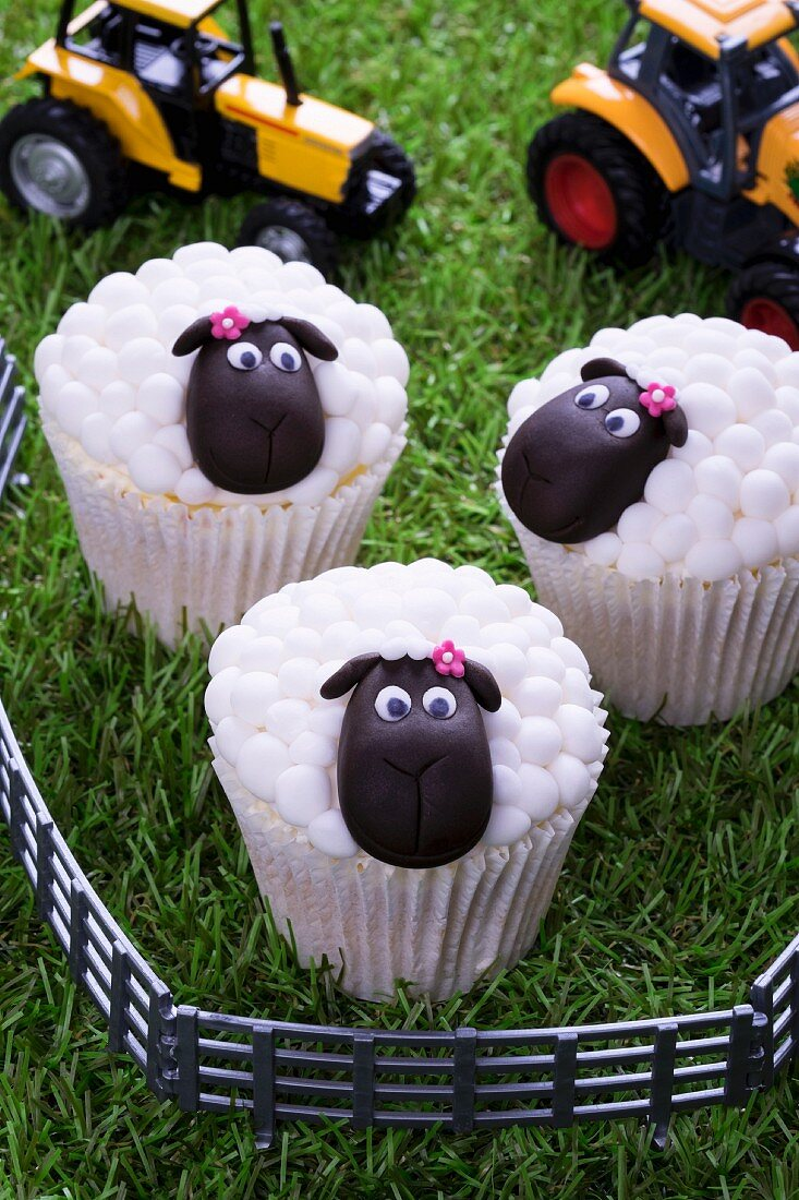 Easter lamb cupcakes and toy tractors on a grass surface