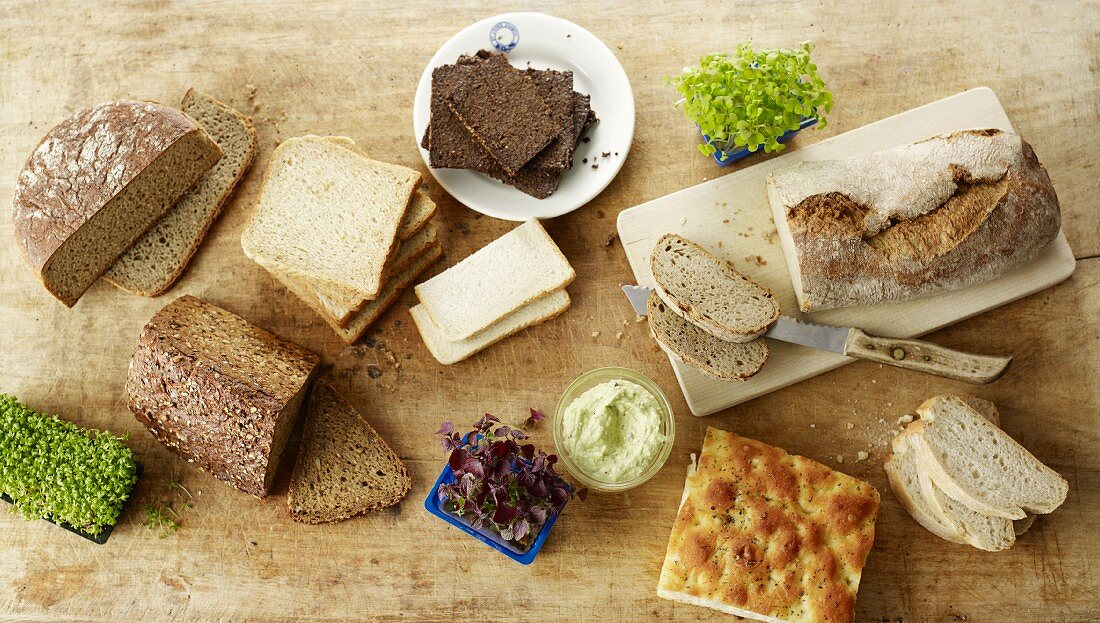 Various breads, cress and spreads on a wooden surface (seen from above)