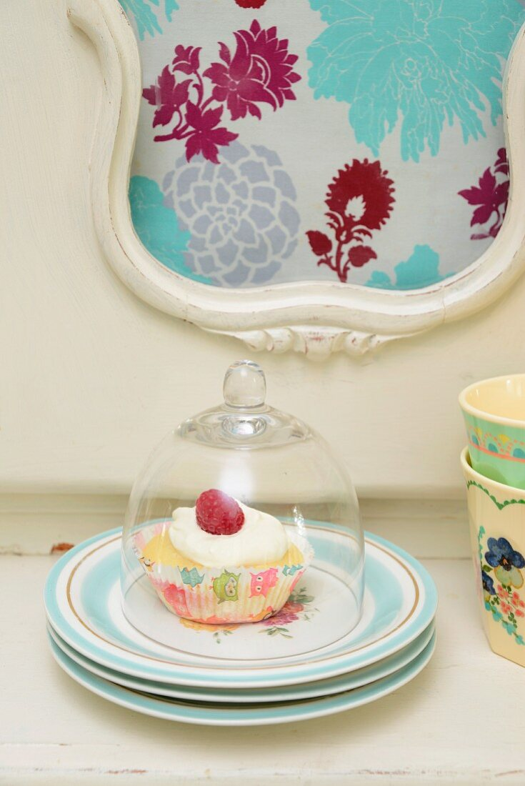 A cupcake decorated with raspberries on a stack of floral-patterend plates under a glass cloche on a 1940's cake buffet