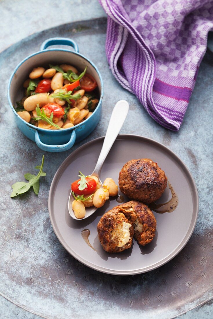 Meatball filled with feta cheese and served with a white bean medley