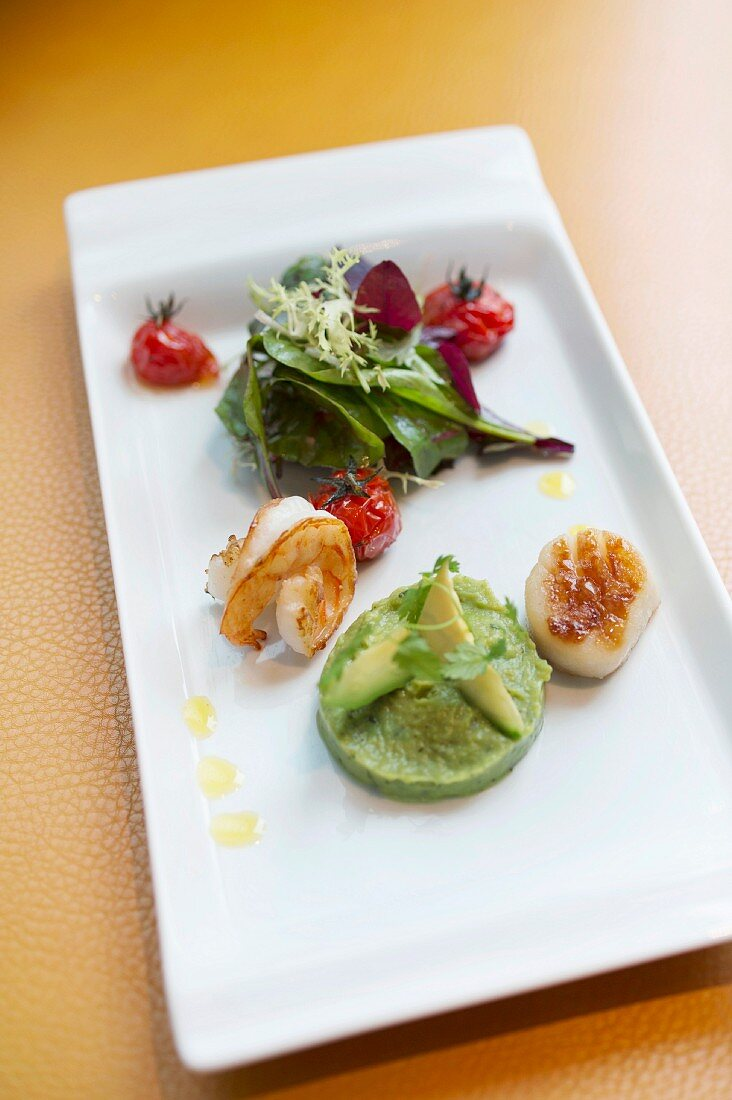 Scallops and fried king prawns on an avocado salsa with mini oven-roasted tomatoes, restaurant 'Henricus' in Dresden