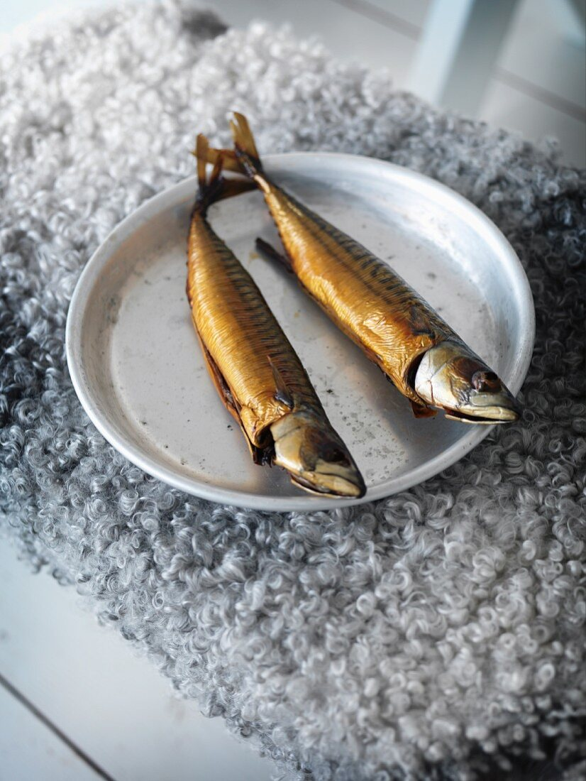 Two smoked fish on plate