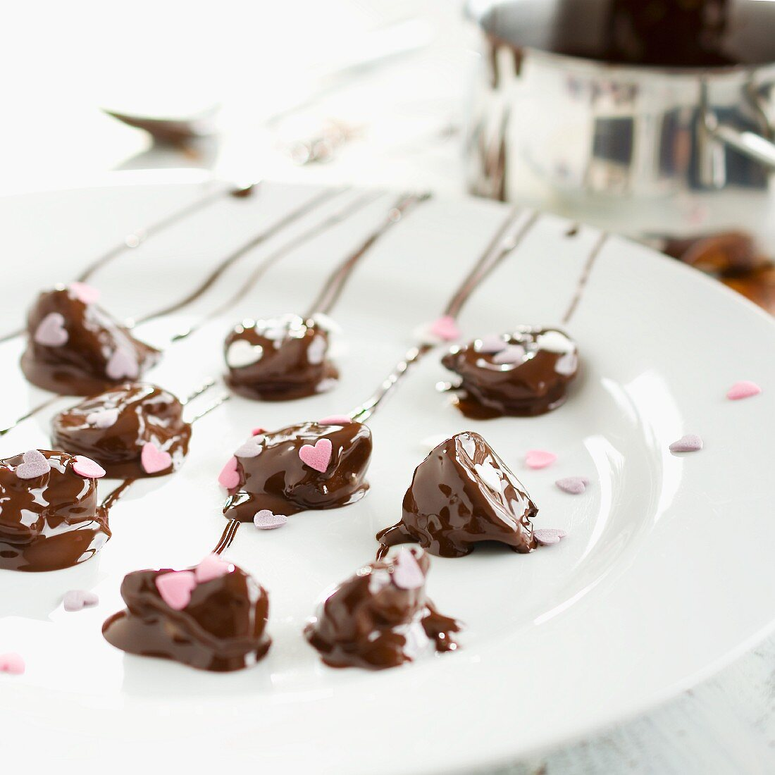 Chocolate-covered plums decorated with sugar hearts being made