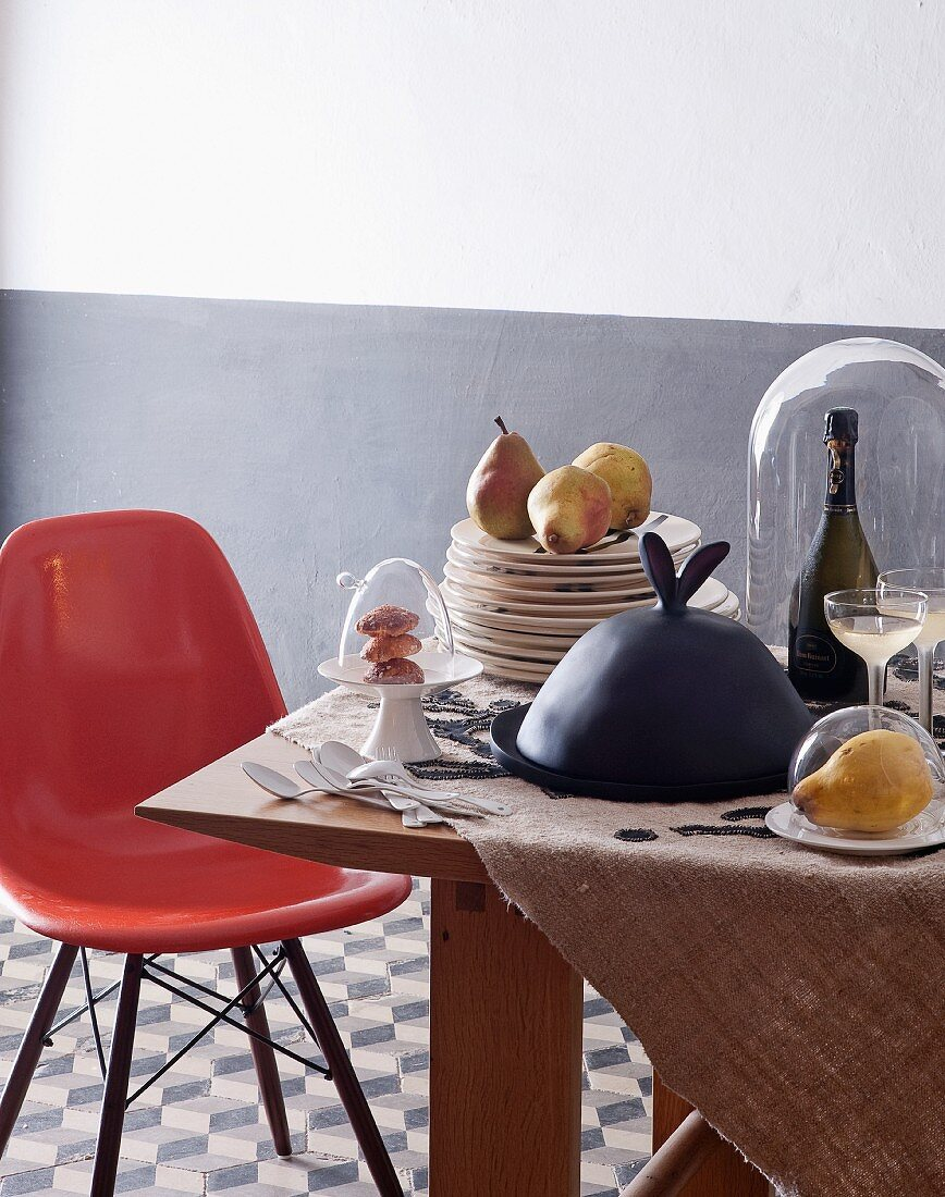 Eames chair at wooden table with stacked plated, food under glass covers and bottle of Champagne