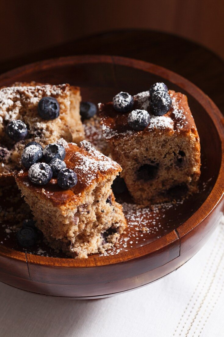 Three slices of blueberry crumble cake in a wooden bowl with icing sugar