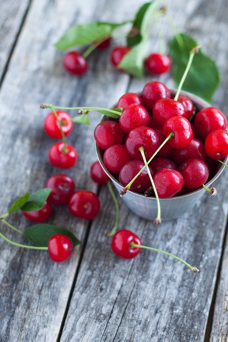 Fresh cherries in a metal bowl on a wooden surface