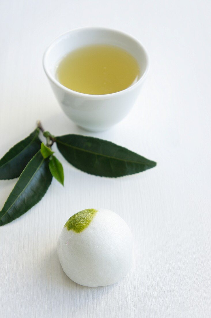 Daifuku mochi (Japanese sweet) with a sprig of tea leaves and a bowl of green tea