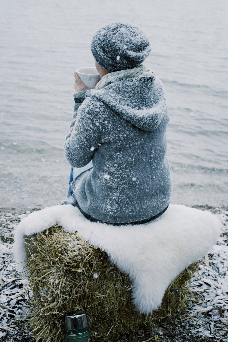 A woman sitting on a river bank in the snow with a cup of tea