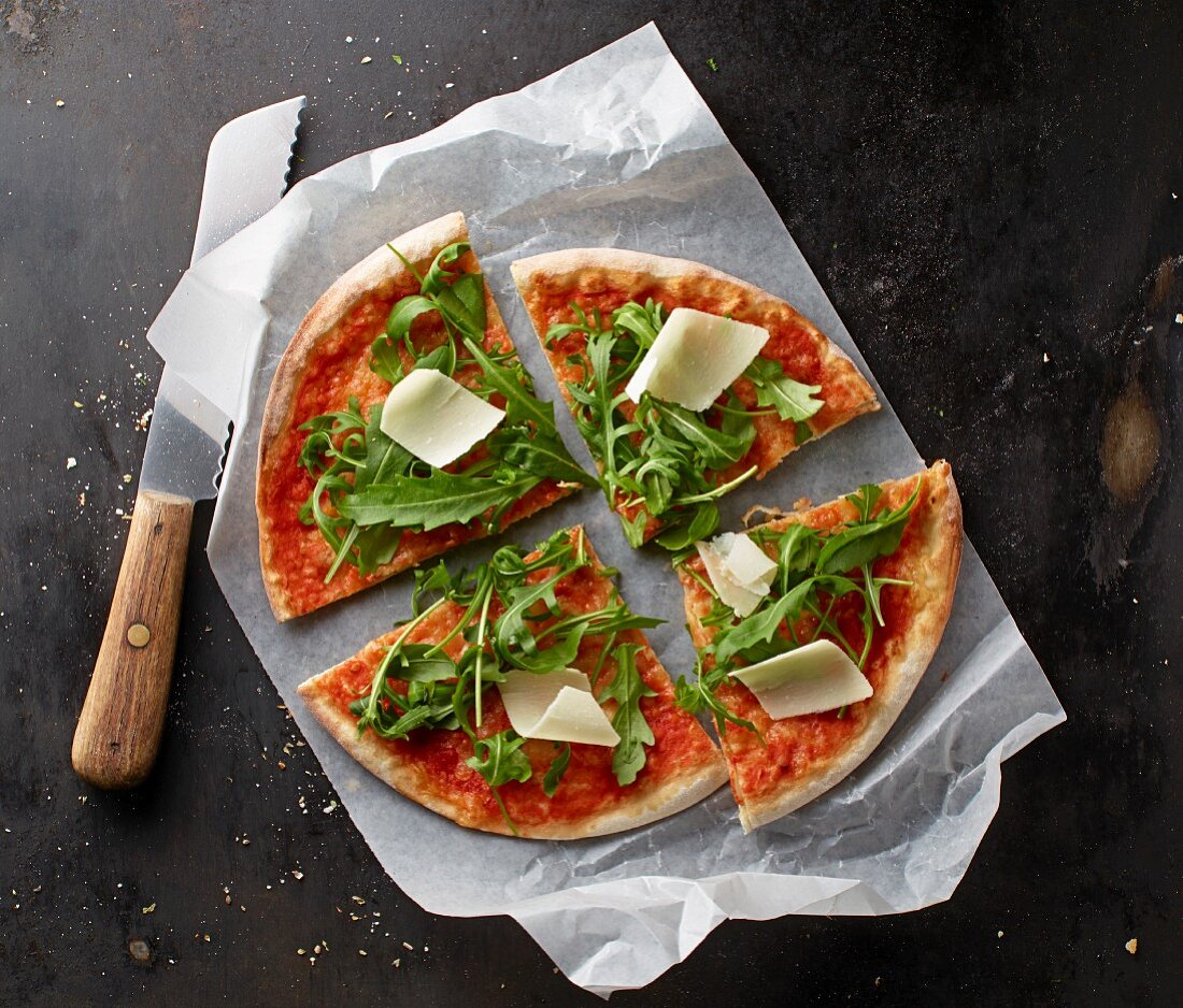 Pizza Margherita with rocket and Parmesan cheese on a piece of paper with a knife