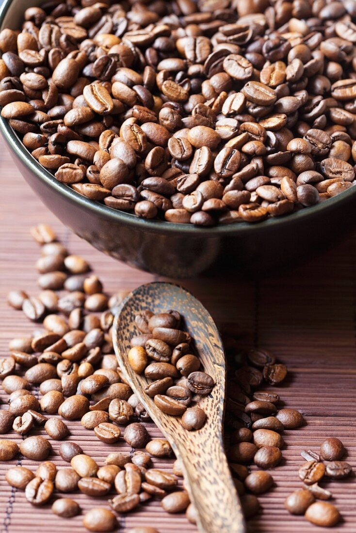 Coffee beans in a bowl and on a spoon