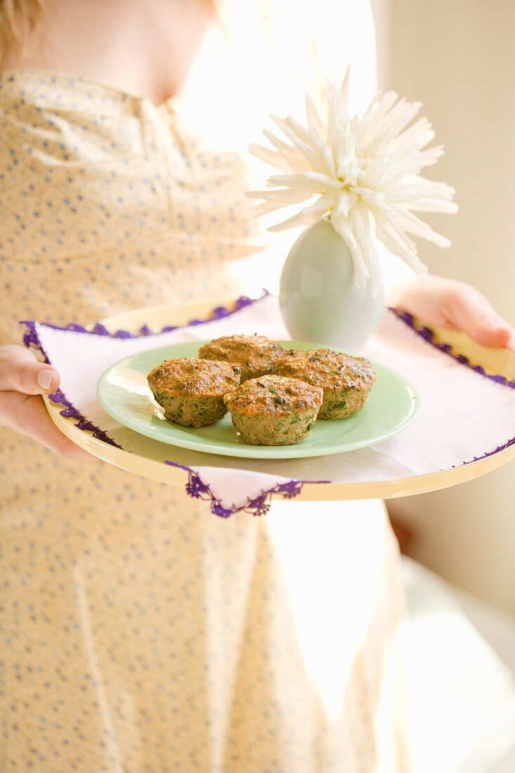 A woman holding a tray of savoury cupcakes made from minced beef and vegetables